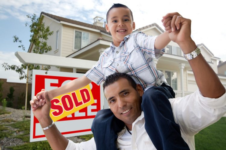 Hispanic Father and Son in Front of Their New Home with Sold Hom.