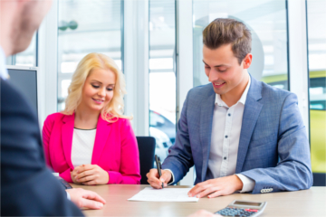 Couple buying car at dealership and signing sales contract with salesman